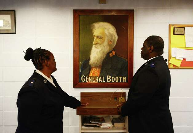 Troy Salvation Army envoys, Vangerl, left, and James Pegues, stand next to a portrait of Salvation Army founder, William Booth,  Wednesday May, 13, 2015, at the Salvation Army Chapel in Troy, N.Y. The Troy group recently celebrated their 130th anniversary.  (Will Waldron/Times Union) Photo: WW / 00031817A
