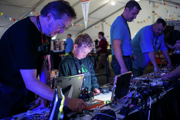 Jim Gale (left) and Lucas Dennison test out products at the Microsoft table for the Maker Faire, which will be in San Mateo this weekend.