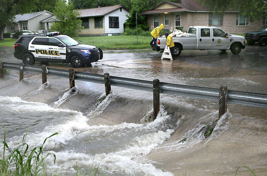 A San Antonio Police vehicle blocks a flooded road in Balcones Heights as city workers set up baracades this month. As contract negotiations continue between the police and the city, a reader remembers all the risks police confront. Photo: Bob Owen /San Antonio Express-News / ©2015 San Antonio Express-News