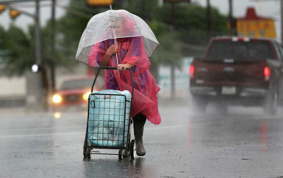 Natalie Rice, protected by plastic and umbrella, struggles through a torential rain as she walks to her job along Fredericksburg Road. With all the downpours in San Antonio this summer, a reader offers a suggestion when it comes to water restrictions. Photo: Bob Owen /San Antonio Express-News / ©2015 San Antonio Express-News