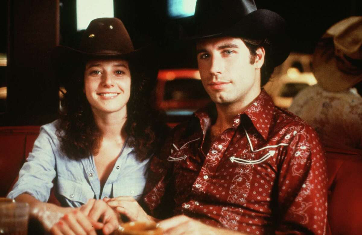 'Urban Cowboy' stars: Then & now Actor John Travolta and Debra Winger pose in a scene during the Paramount Pictures movie 'Urban Cowboy