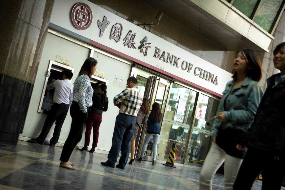 People walk past a Bank of China branch as customers wait to use ATMs in Beijing. Bank of China is one of several large, state-owned Chinese banks that has been identified as facilitating credit card payments for online sales of fake goods or holding accounts for alleged counterfeiters. Photo: Mark Schiefelbein /Associated Press / AP