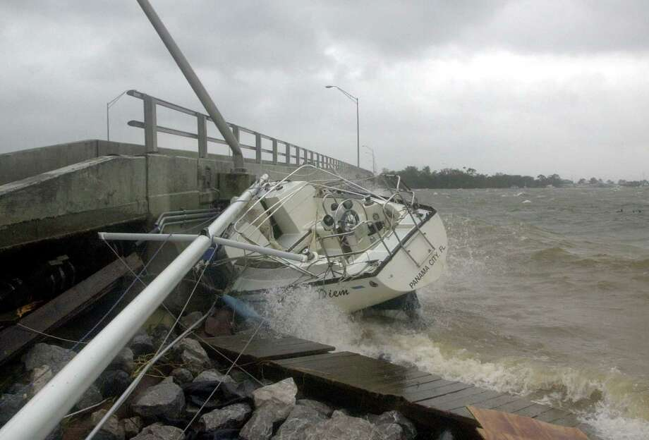 Waves crash against a sailboat lodged under a bridge in Fort Walton Beach, Fla., on Sept. 16, 2004, after Hurricane Ivan struck the Gulf Coast. In the following week Ivan looped around and made landfall again near Cameron, La. Photo: John Bazemore /Associated Press / AP