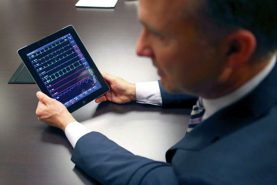 AirStrip's president, Dr. Matt Patterson, demonstrates the company's mobile applications that are used by hospitals and doctors to monitor patients' health in real time. Photo: William Luther /San Antonio Express-News / © 2015 San Antonio Express-News