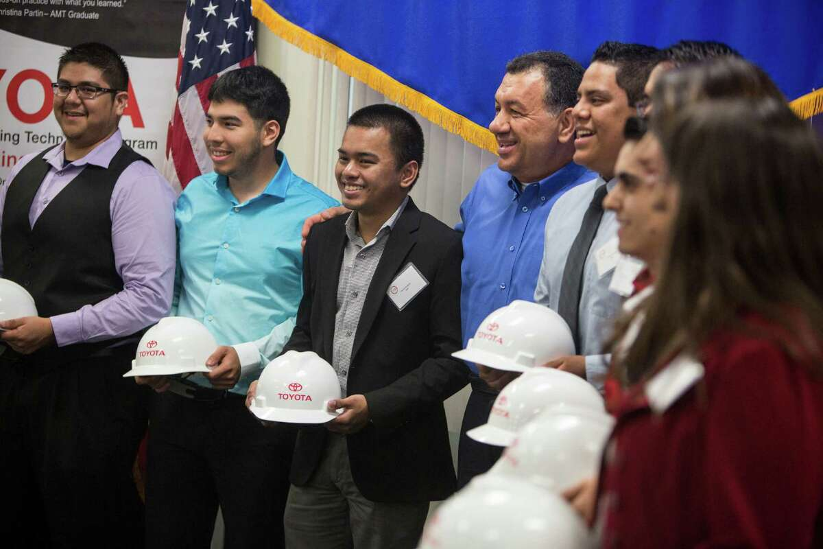 The graduates who are being hired by Toyota Texas stand for a picture with President Joe DaRosa (in blue shirt) during a ceremony to honor the graduates Friday.The program allows students to work for the company while earning their degrees.