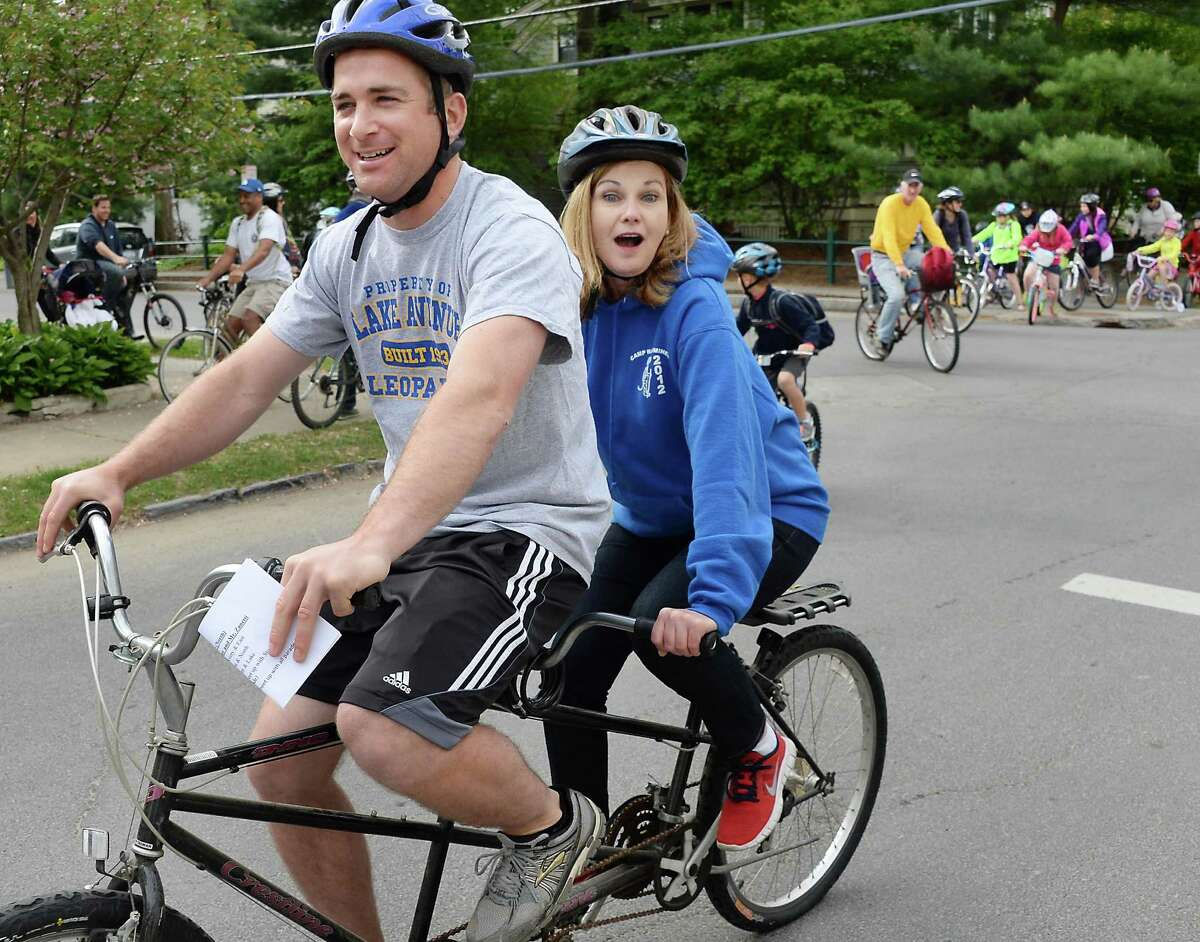 Gym teacher Jake Zanetti, left, and Principal Barbara Messier ride a tandem bike as they lead students, parents and teachers to Lake Avenue Elementary School on National Bike to Work Day Friday May 15, 2015 in Saratoga Springs, NY. (John Carl D'Annibale / Times Union)