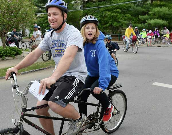 Gym teacher Jake Zanetti, left, and Principal Barbara Messier ride a tandem bike as they lead students, parents and teachers to Lake Avenue Elementary School on National Bike to Work Day Friday May 15, 2015 in Saratoga Springs, NY.  (John Carl D'Annibale / Times Union) Photo: John Carl D'Annibale / 00031797A