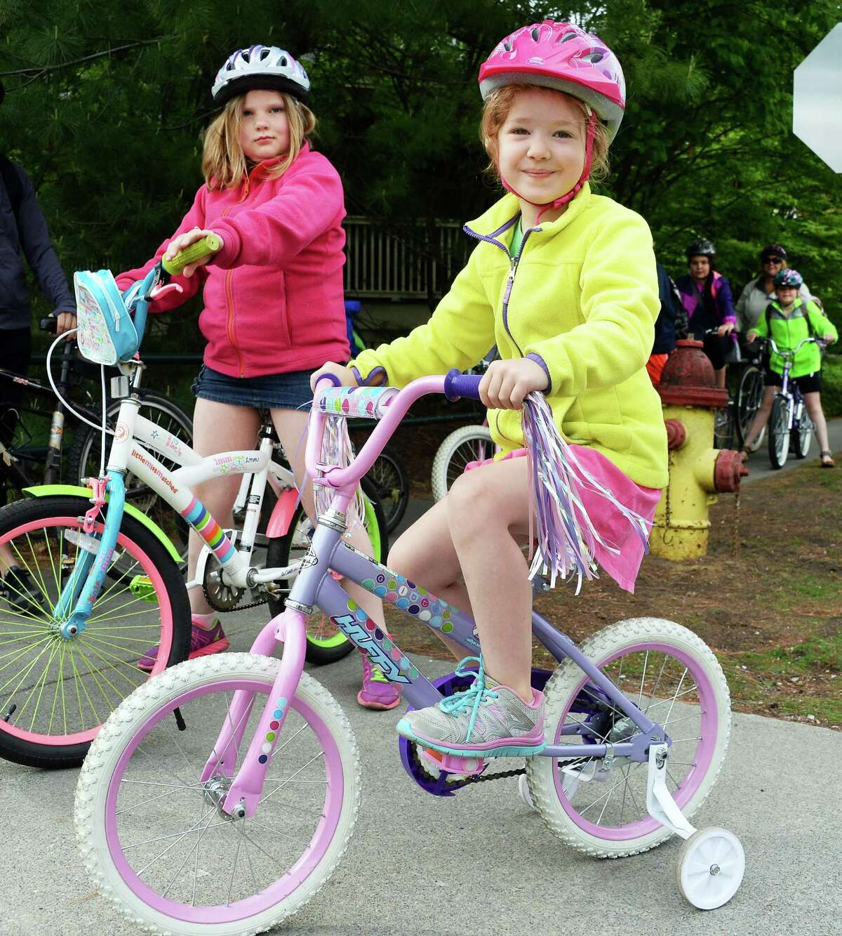 Lake Avenue Elementary School students Rachel Haarman, left, 8, and Abigail Norsworthy, 5, bicycle to school on National Bike to Work Day Friday May 15, 2015 in Saratoga Springs, NY. (John Carl D'Annibale / Times Union)