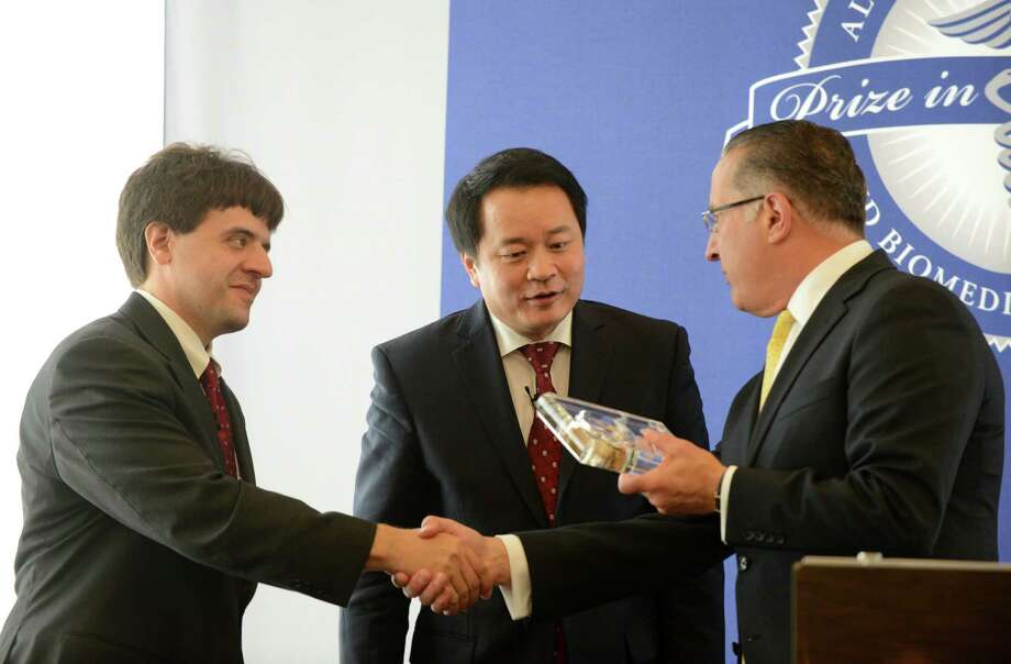 Dr. Karl Deisseroth, left, and Dr. Xiaoling Sunney Xie, center, are presented with the $500,000 Albany Medical Center Prize in Biomedicine and Biomedical Research by Dr. Vince Verdile, dean of Albany Medical College, during an awards ceremony Friday, May 15, 2015, in Albany, N.Y. Karl Deisseroth, a professor at Stanford University, has been recognized for his work developing methods that allow scientists to understand how the brain's circuitry works, and how specific neurons play a role in conditions like Parkinson's disease, addiction and depression, as well as normal processes like memory and learning. Xiaoliang Sunney Xie of Harvard University was selected for work that allows scientists to pinpoint genomic changes in a single cell. His work has major implications in such fields as cancer research and in-vitro fertilization. (Will Waldron/Times Union) Photo: WW / 00031792A