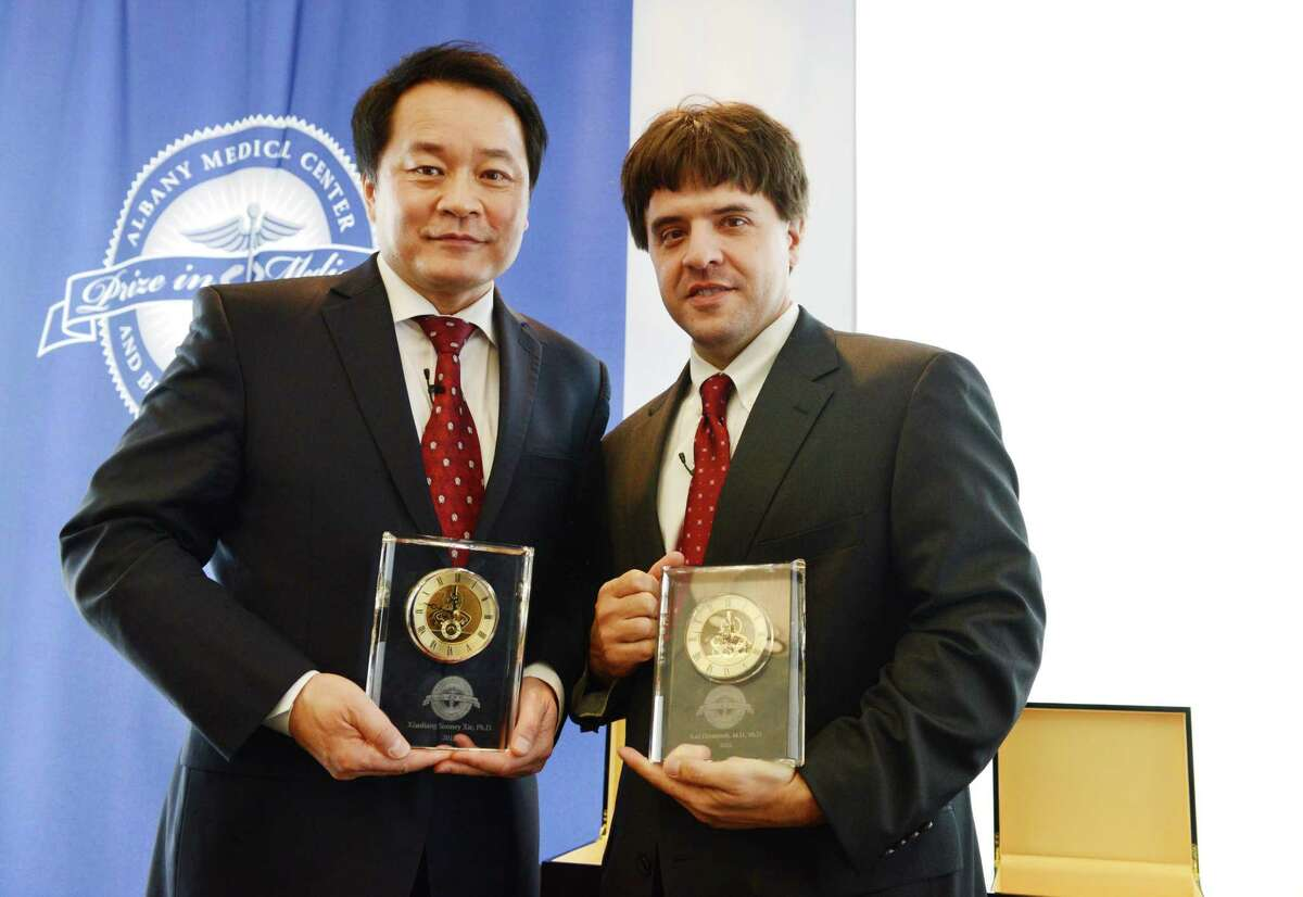 Dr. Xiaoling Sunney Xie, left, and Dr. Karl Deisseroth hold their plaques after receiving the $500,000 Albany Medical Center Prize in Biomedicine and Biomedical Research during an awards ceremony Friday, May 15, 2015, in Albany, N.Y. Karl Deisseroth, a professor at Stanford University, has been recognized for his work developing methods that allow scientists to understand how the brain?'s circuitry works, and how specific neurons play a role in conditions like Parkinson?'s disease, addiction and depression, as well as normal processes like memory and learning. Xiaoliang Sunney Xie of Harvard University was selected for work that allows scientists to pinpoint genomic changes in a single cell. His work has major implications in such fields as cancer research and in-vitro fertilization. (Will Waldron/Times Union)