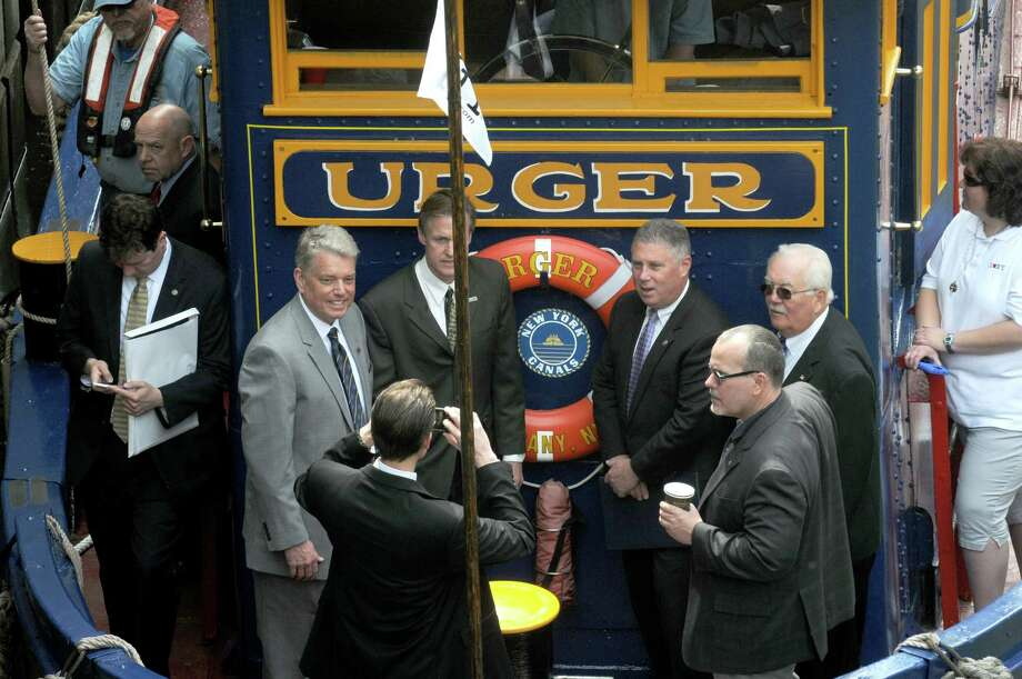 Canal Corporation Director Brian U. Stratton, left, and and local officials get their photograph taken on the bow of the tug Urger as it enters Lock E2 during a 100th Anniversary celebration of the opening of the Waterford flight of locks and the seasonal opening of the canal system on Friday May 15, 2015 in Waterford, N.Y. (Michael P. Farrell/Times Union) Photo: Michael P. Farrell / 00031858A