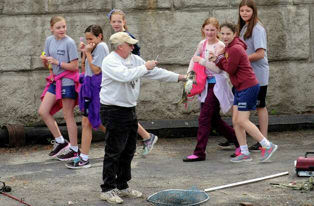 Students from St. Mary's Catholic School of Waterford react to a fishermans's catch during a 100th Anniversary celebration of the opening of the Waterford flight of locks and the seasonal opening of the canal system on Friday May 15, 2015 in Waterford, N.Y. (Michael P. Farrell/Times Union) Photo: Michael P. Farrell / 00031858A