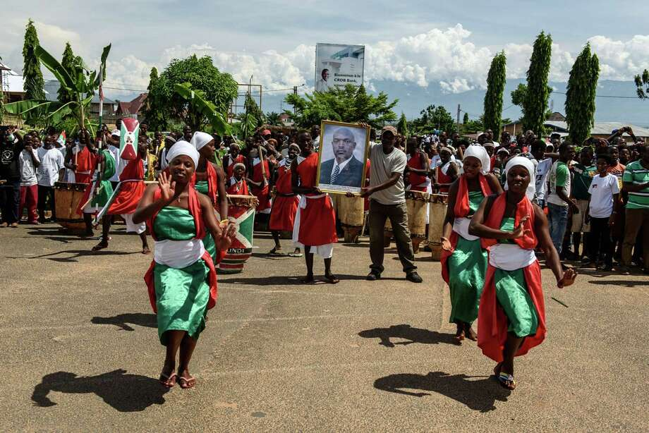 Women celebrate in the street Friday as people hold a portrait of Burundi President Pierre Nkurunziza in the capital of Bujumbura. The government says it defeated a coup attempt, and the president called for calm. Photo: JENNIFER HUXTA, Stringer / AFP