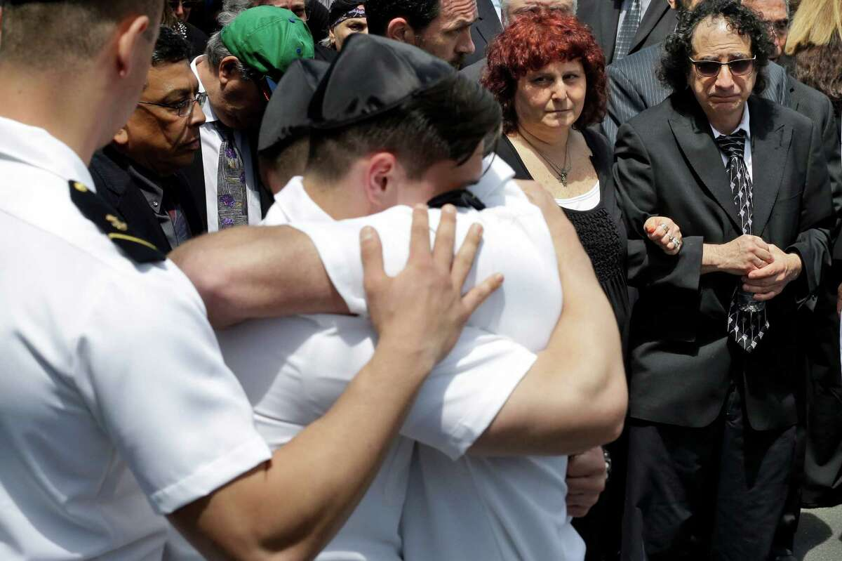 Howard and Susan Zemser (right) watch as midshipmen embrace May 15, 2015, during the the funeral service for the Zemsers' son, U.S. Naval Academy midshipman Justin Zemser at Boulevard-Riverside-Hewlett Chapel in Hewlett, N.Y. The 20-year-old sophomore was traveling from the academy in Annapolis, Maryland, to his home in New York City when he was killed in Tuesday's derailment in Philadelphia. He was one of eight people killed.