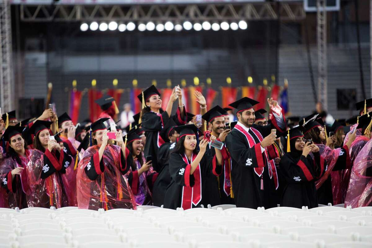 University of Houston graduates stand up for the arrival of actor Matthew McConaughey, many trying to capture footage of the well-known Longhorn's entrance to the UH commencement ceremony Friday.