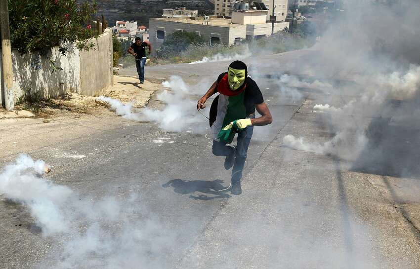 Palestinian demonstrators run for cover from teargas fired during clashes with Israeli security forces following a demonstration to mark the 67th anniversary of the