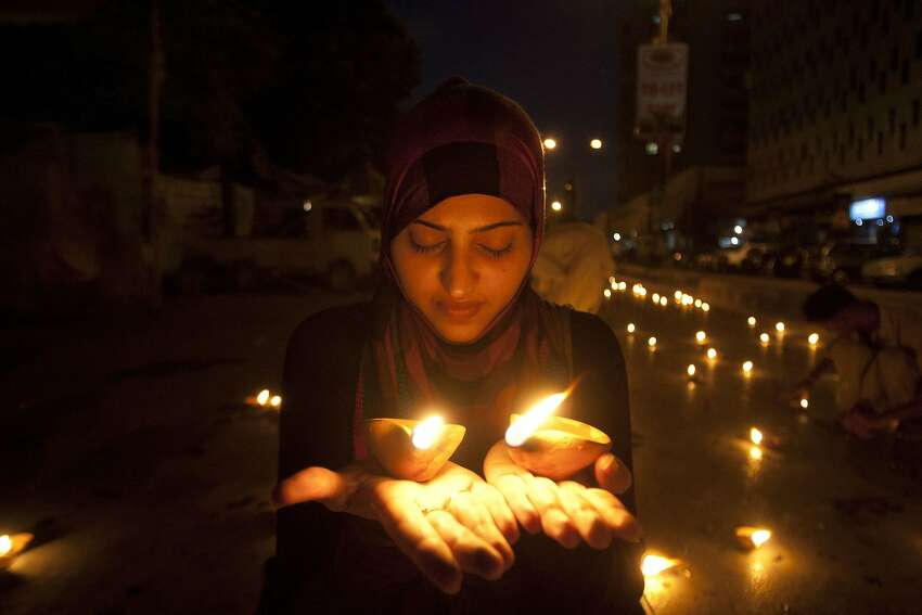 A Pakistani girl holds earthen lamps during a vigil to pay tribute to the victims of Wednesday's bus attack, in Karachi, Pakistan, Friday, May 15, 2015. Unidentified gunmen killed 45 minority Shiites in an attack on a bus in the southern city of Karachi.