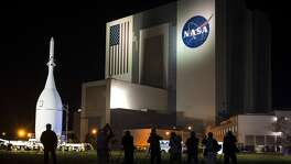 "The Vehicle Assembly Building at Kennedy Space Center is where the Apollo/Saturn crafts and, later, the shuttles were assembled. ""Each of its four doors opens wide enough to take in the United Nations building and tall enough to take in most skyscrapers,"" Dean writes. ""Its volume is three-and-a-half times that of the Empire State Building. Its roof is big enough to contain more than six football fields."" Photo: Orion spacecraft passes the Vehicle Assembly Building (VAB) on the way to the launch pad in preparation for Exploration Flight Test 1 (EFT-1) on Tuesday, Nov. 11, 2014, at the Kennedy Space Center."