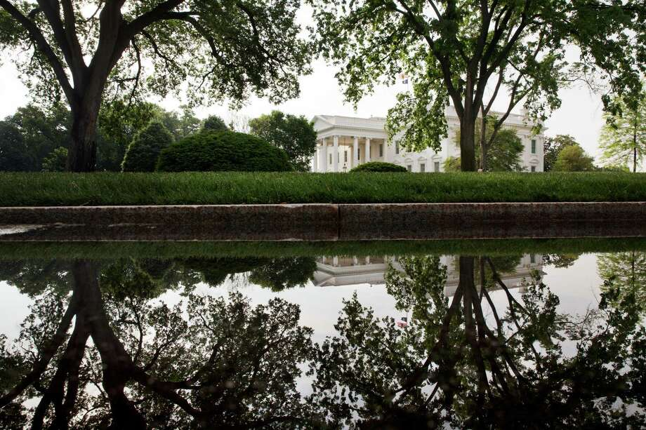 The White House and trees are reflected in a puddle on the White House complex, Saturday, May 16, 2015, in Washington. The Pentagon says U.S. commandos have mounted a rare raid in eastern Syria, killing the Islamic State commander in charge of oil fields in a firefight and capturing his wife. Photo: Jacquelyn Martin, AP / AP