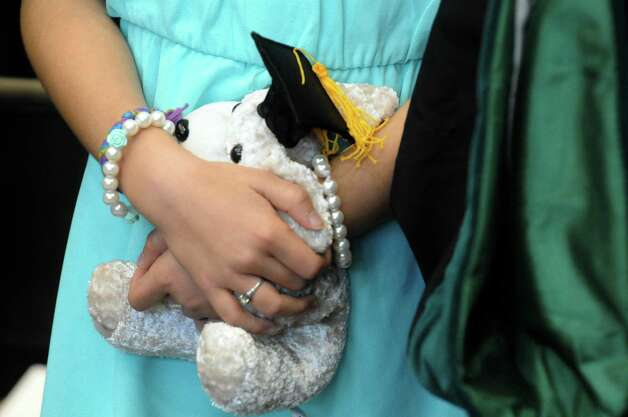Nine-year-old Alana DeLude of Delmar holds a graduation stuffed animal as she walks in the proccesion with her mother graduate Susan Paurowski during the Sage Colleges Commencement at the RPI Field House on Saturday May 16, 2015 in Troy, N.Y. (Michael P. Farrell/Times Union) Photo: Michael P. Farrell / 00031510A