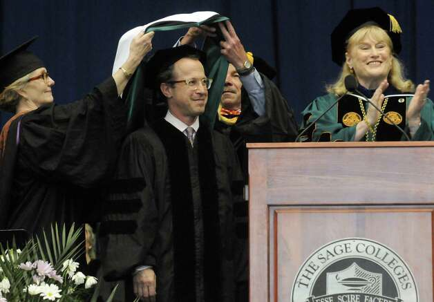 David Alan Miller, left, Albany Symphony's Music Director and Conductor receives and honorary degree during the Sage Colleges Commencement at the RPI Field House on Saturday May 16, 2015 in Troy, N.Y. (Michael P. Farrell/Times Union) Photo: Michael P. Farrell / 00031510A
