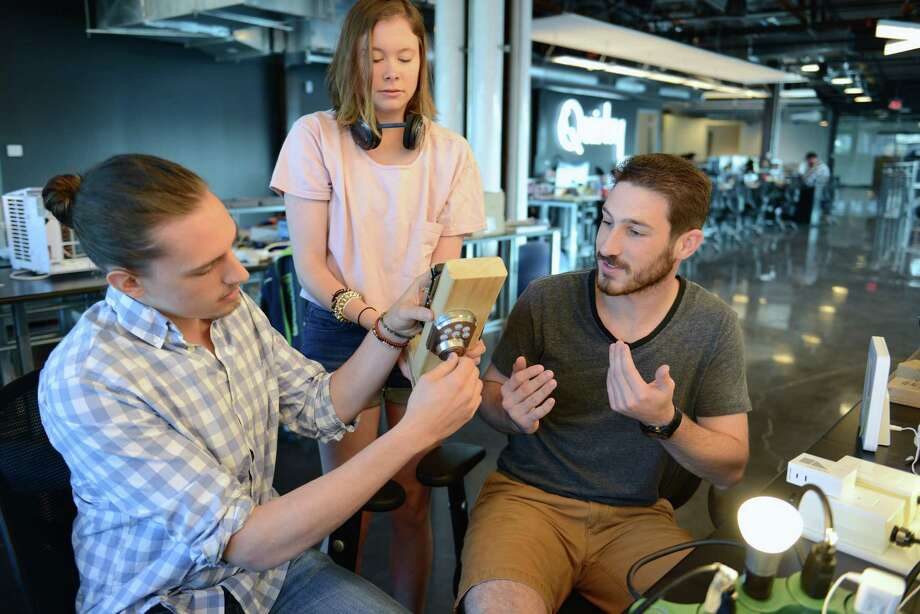 Nick Sheridan, left, Natalie Rergich and Anthony Tedesco, right, of Quirky in the Schenectady office work on the Kwikset Electronic Deadbolt, which allows users to unlock and lock from anywhere using their phone. (Courtesy Quirky)