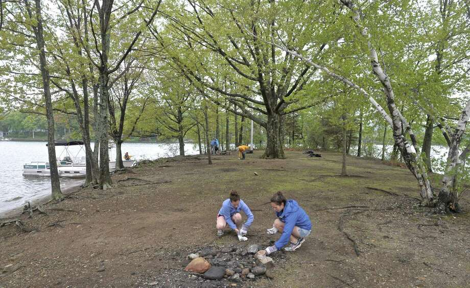 Katherine DeFazio, 17, and Amanda Deming, 17, pick up broken glass from Sand Island in Candlewood Lake during the 15th Annual John Marsicano Memorial Lake Cleanup, on Saturday, May 16, 2015, in New Fairfield, Conn. DeFazio and Deming are both from Bethel and take part in Project CLEAR (Candlewood Lake Environmental Awareness and Responsibility Project), which is an experiential science program for diverse high school students from school districts in northwestern Connecticut and the greater Danbury area, they attend Bethel High School. Photo: H John Voorhees III / The News-Times