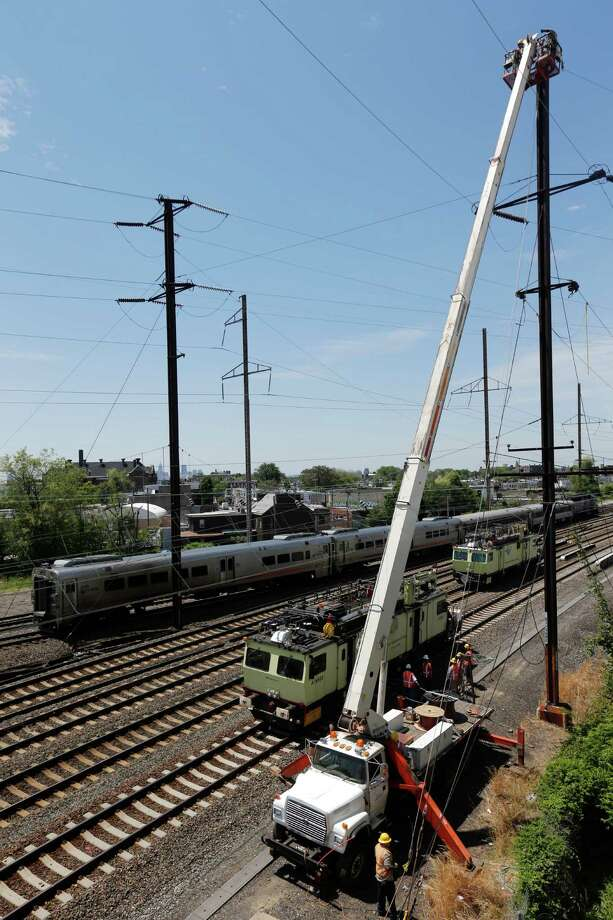 A New Jersey Transit train, back, rolls by as workers labor at the site where a deadly train derailment occurred earlier in the week, Friday, May 15, 2015, in Philadelphia. Amtrak is working to restore Northeast Corridor rail service between New York City and Philadelphia. Service was suspended after a train derailed in Philadelphia on Tuesday night, killing eight passengers and injuring more than 200. (AP Photo/Julio Cortez) Photo: Julio Cortez, STF / Associated Press / AP
