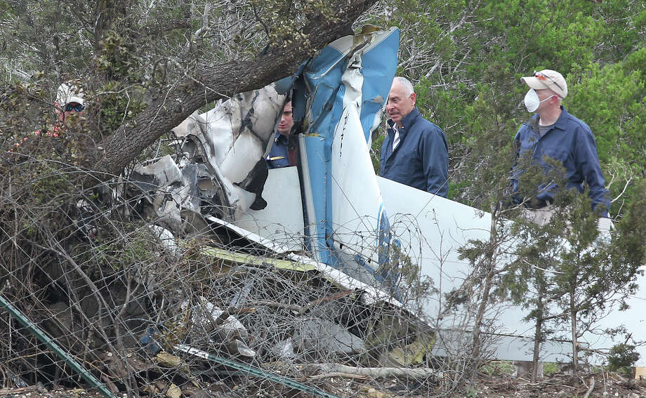 Officials inspect the mangled wreckage after a small aircraft crashes into a wooded area adjacent to the back parking lot of Strutty's  Feed and Pet Supply just across Highway 281from Kestrel Air Park in Bulverde on Saturday, May16, 2025.  Several bodies are removed from the scene. Photo: Tom Reel, San Antonio Express-News