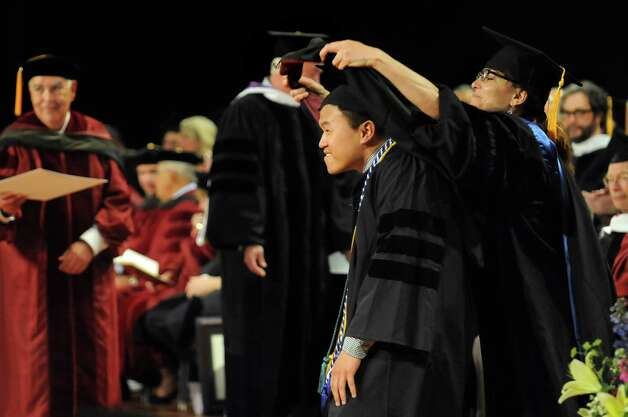 Graduate Jin Feng Huang, center, is hooded as Doctor of Pharmacy during the Albany College of Pharmacy commencement exercises on Saturday, May 16, 2015, at the Empire State Plaza Convention Center in Albany, N.Y. (Cindy Schultz / Times Union) Photo: Cindy Schultz / 00031495A