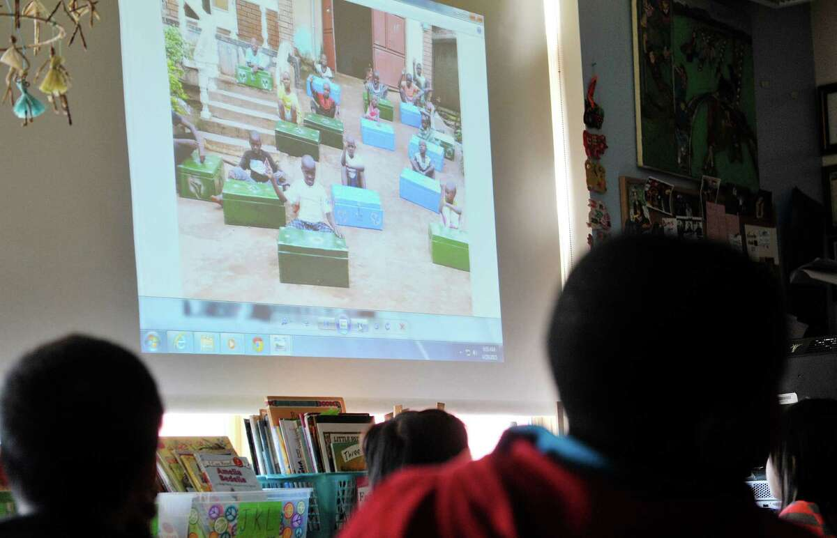 Second grade students at Delaware Community School look over photographs of boys living at an orphanage in Kampala, Uganda on Wednesday, April 29, 2015, in Albany, N.Y. Last month the students spoke with the boys in Uganda by way of Skype. The second graders then worked to raise money to buy mosquito nets to protect the Ugandan boys at night from malaria. Diane Reiner, founder of the organization Jajja?'s Kids, has been working to help the boys in Uganda and she was at the Albany school on Wednesday to show the students photographs and to give them cards created by the boys in Uganda. (Paul Buckowski / Times Union)