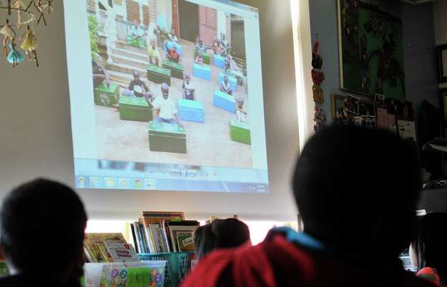 Second grade students at Delaware Community School look over photographs of  boys living at an orphanage in Kampala, Uganda on Wednesday, April 29, 2015, in Albany, N.Y.  Last month the students spoke with the boys in Uganda by way of Skype.  The second graders then worked to raise money to buy  mosquito nets to protect the Ugandan boys at night from malaria.  Diane Reiner, founder of the organization Jajja's Kids, has been working to help the boys in Uganda and she was at the Albany school on Wednesday to show the students photographs and to give them cards created by the boys in Uganda.   (Paul Buckowski / Times Union) Photo: PAUL BUCKOWSKI / 00031633A