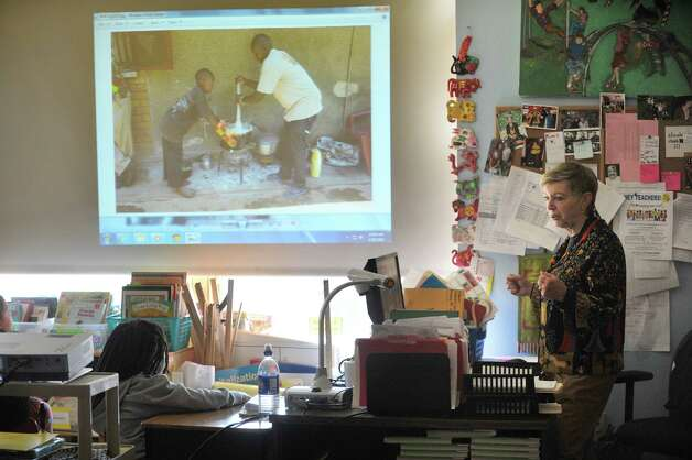 Diane Reiner, right, founder of the organization Jajja's Kids, shows photographs of boys living at an orphanage in Kampala, Uganda on Wednesday, April 29, 2015, at the Delaware Community School in Albany, N.Y.  Last month these second grade students at Delaware Community School spoke with the boys in Uganda by way of Skype. The second graders worked to raise money to buy mosquito nets to protect the Ugandan boys at night from malaria. Diane Reiner was at the Albany school on Wednesday to show the students photographs and to give them cards created by the boys in Uganda. (Paul Buckowski / Times Union) Photo: PAUL BUCKOWSKI / 00031633A