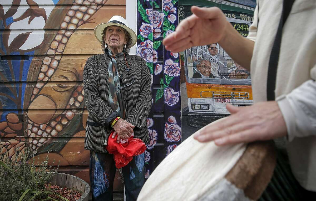 """Anna Halprin, stops along Balmy St. as musicians pass by, to observe the murals during a reenactment of her """"Blank Placard Dance"""" march through the Mission District neighborhood on Sat. May 16, 2015, in San Francisco, Calif."""