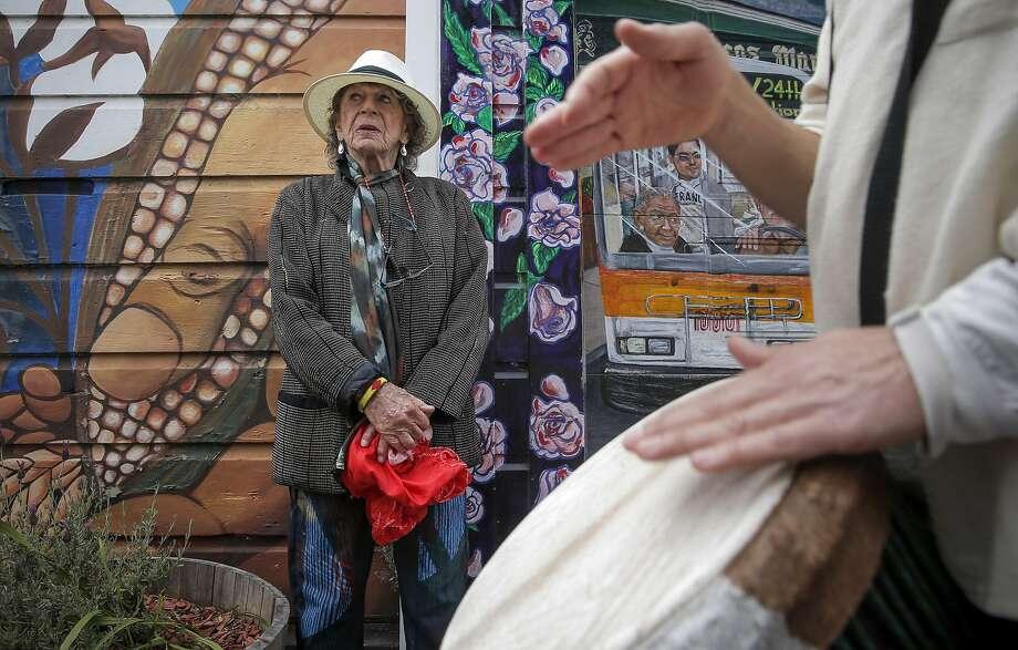 Anna Halprin stops along Balmy Street as musicians pass by. Photo: Michael Macor, The Chronicle