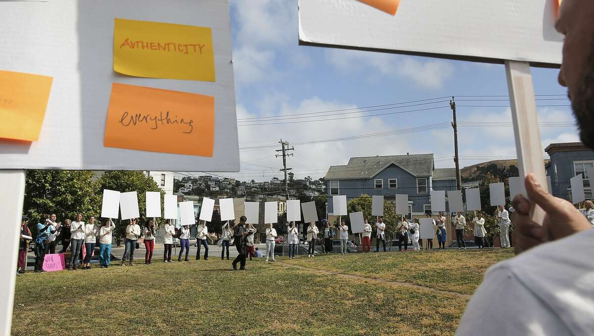 """The reenactment of Anna Halprin's """"Blank Placard Dance"""" ends at Garfield Park following a march through the Mission District neighborhood on Sat. May 16, 2015, in San Francisco, Calif."""