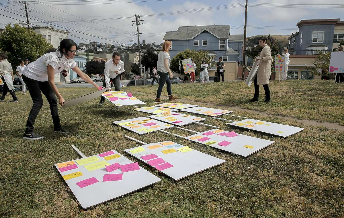 """Marchers place their placards on the grass during a reenactment of Anna Halprin's """"Blank Placard Dance"""" that marched through the Mission District neighborhood on Sat. May 16, 2015, in San Francisco, Calif."""
