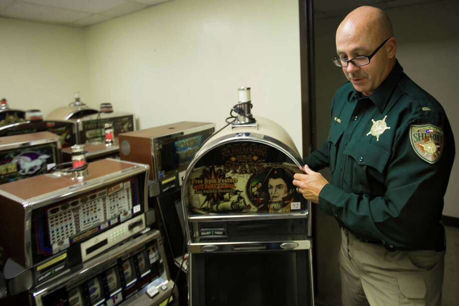Galveston County Sheriff Lieutenant Ron Hill displays one of the hundreds of gaming machines the county has confiscated. Sheriff Henry Trochesset says the machines are proof that illegal gambling has worsened. Photo: Marie D. De Jesus, Staff / © 2015 Houston Chronicle