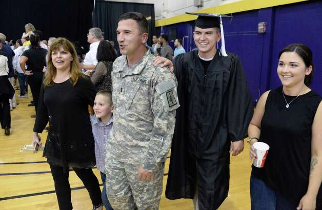 The Houghtaling family of Colonie, from left, mother Rhonda, grandson Zacharia, father, US Army 1st Lt. Frank, son Frankie and sister Brittany, reunited at Frankie's UAlbany graduation Saturday May 16, 2015 in Albany, NY. A chaplin with the 102nd MP BN Forward, Frank surprised his family by secretly returning from duty in Cuba and appearing as the UAlbany mascot during the UAlbany Sociology Dept. Undergrad Graduation Recognition Ceremony.  (John Carl D'Annibale / Times Union) Photo: John Carl D'Annibale / 10031834A