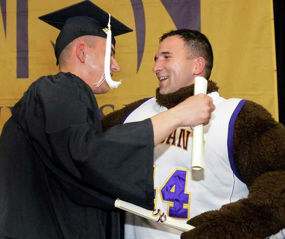 Grad Frankie Houghtaling, left, Colonie is surprised when the school's mascot is revealed to be his father, 1st Lt. Frank Houghtaling who secretly returned from duty in Cuba to attend his son's graduation during  UAlbany Sociology Dept. Undergrad Graduation Recognition Ceremony Saturday May 16, 2015 in Albany, NY. (John Carl D'Annibale / Times Union) Photo: John Carl D'Annibale / 10031834A