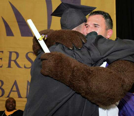 Grad Frankie Houghtaling of Colonie, left, is surprised when the school's mascot is revealed to be his father, 1st Lt. Frank Houghtaling who secretly returned from duty in Cuba to attend his son's graduation during  UAlbany Sociology Dept. Undergrad Graduation Recognition Ceremony Saturday May 16, 2015 in Albany, NY. (John Carl D'Annibale / Times Union) Photo: John Carl D'Annibale / 10031834A