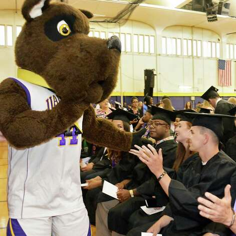 Frankie Houghtalingof Colonie, right, high fives the school's mascot unaware that it is his father, 1st Lt. Frank Houghtaling who secretly returned from duty in Cuba to attend his sonOs graduation during  UAlbany Sociology Dept. Undergrad Graduation Recognition Ceremony Saturday May 16, 2015 in Albany, NY. (John Carl D'Annibale / Times Union) Photo: John Carl D'Annibale / 10031834A