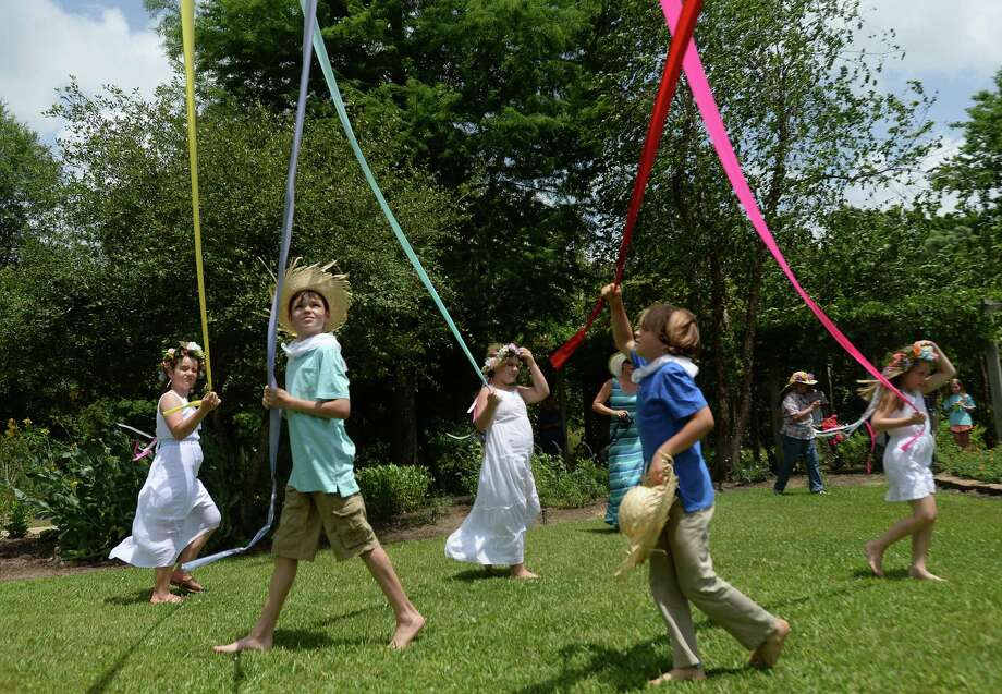 """Children make their way round, each wrapping a colorful ribbon as they go, during the inaugural Maypole Festival held at Beaumont Botanical Gardens Saturday. The pole was erected in memory of Paula Marie Salter, aka """"Torchy,"""" who was an active member of the community and remembered by friends for her bright and giving spirit. The tradition of the springtime maypole dance dates back to 14th century Europe. Photo taken Thursday, May 14, 2015 Kim Brent/The Enterprise Photo: Kim Brent / Beaumont Enterprise"""