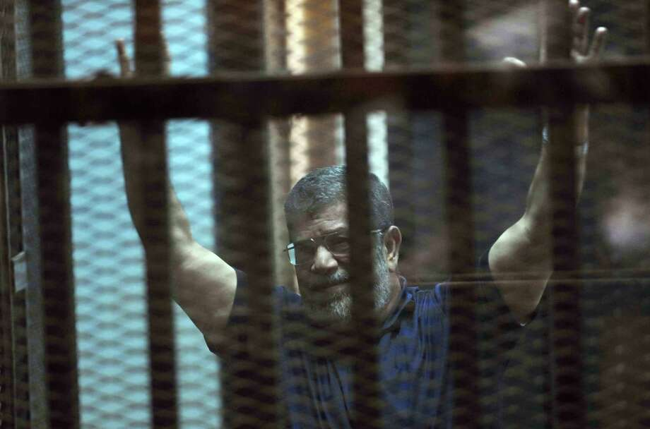 Ousted Egyptian President Mohammed Morsi raises his hands as he sits behind glass in a courtroom. A judge on Saturday sentenced him to death. Photo: Ahmed Omar /Associated Press / AP