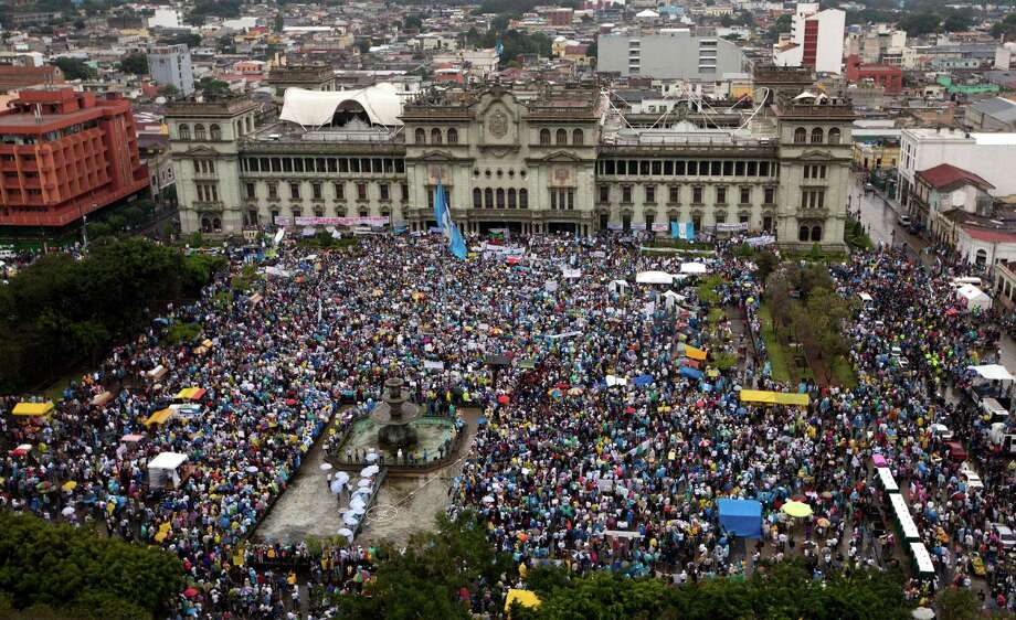 Protesters gather outside the National Palace to demand the resignation of Guatemalan President Otto Perez Molina in Guatemala City, Saturday, May 16, 2015. The protest comes after Perez Molina's Vice President, Roxana Baldetti, resigned on Friday, May 8, amid a customs corruption scandal. (AP Photo/Moises Castillo) Photo: Moises Castillo, STF / AP