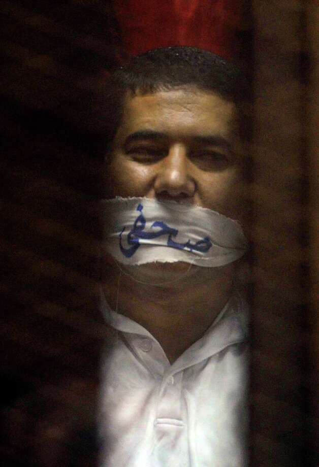 """Egyptian journalist Ibrahim el Darawy wears a cloth over his mouth with Arabic that reads, """"journalists."""" Photo: Ahmed Omar, STR / AP"""