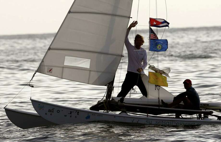 Second place sailor Seth Salzmann waves alongside teammate Wade Miller on their catamaran. Photo: Desmond Boylan, STR / AP