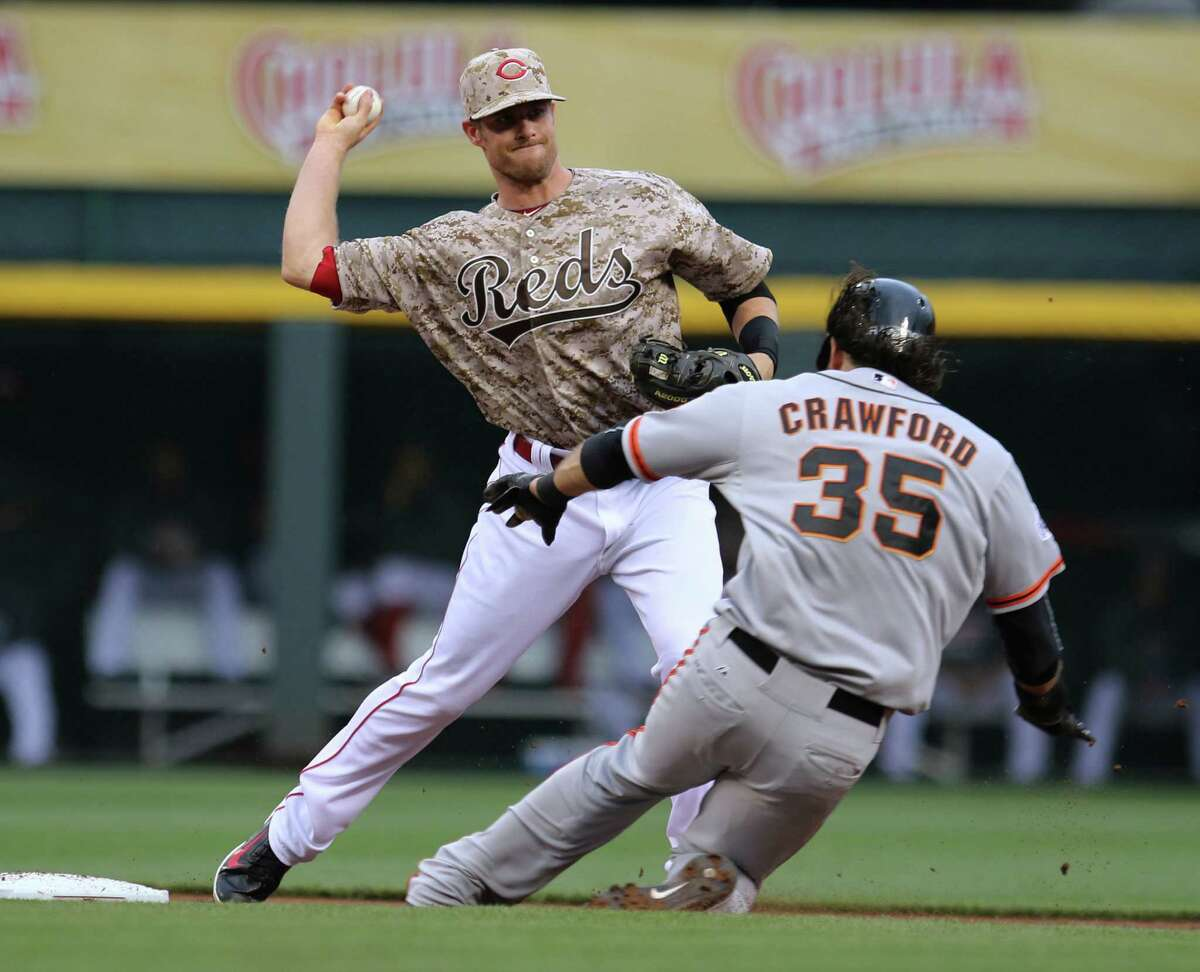 Cincinnati Reds shortstop Zack Cozart (2) throws to first after forcing out San Francisco Giants' Brandon Crawford (35) during the second inning of a baseball game Saturday, May 16, 2015, in Cincinnati. Casey McGehee was out at first on the double play. (AP Photo/Gary Landers)