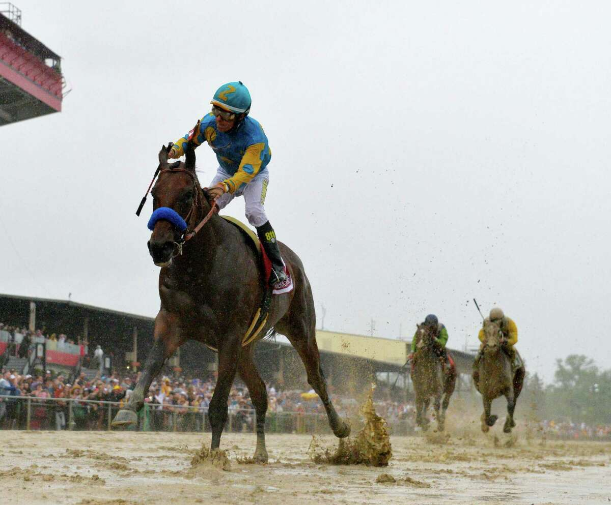 American Pharaoh with jockey Victor Espinoza flies across a very muddy track to win the 140th running of the Preakness Stakes held at Pimlico Race Course Saturday evening May 16, 2015 in Baltimore, Md. The thoroughbred, the 12th Triple Crown winner in history, was elected to National Museum of Racing and Hall of Fame on Wednesday. (Skip Dickstein/Times Union)