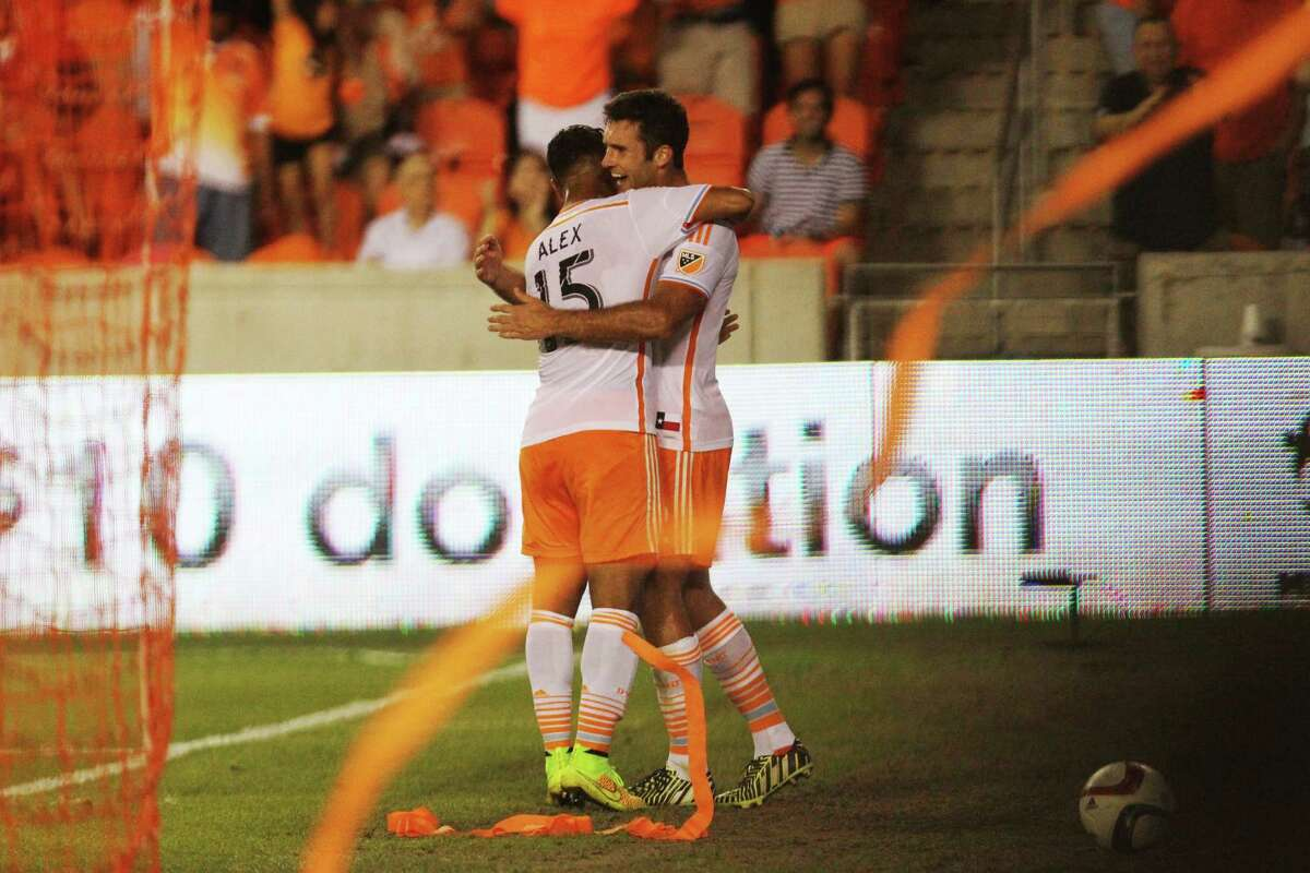 Houston Dynamo midfielder Alexander Lopez (15) embraces Houston Dynamo forward Will Bruin (12), right, after Bruin scored a goal during the second half of the game against the Portland Timber, Saturday, May 16, 2015, in Houston.